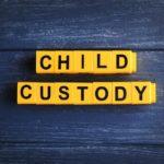 Text CHILD CUSTODY made of yellow blocks on wooden background, closeup